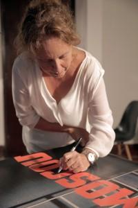 """Jordana assinando o cartaz do documentário """"Moscou"""""""