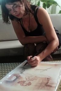 Rosana Urbes assinando o poster do filme, para compor a galeria da AIC.