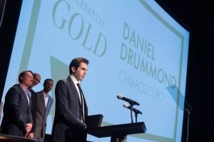 Daniel Drummond recebendo o prêmio e atrás Roy Conli,  Don Hall e Chris Williams (time vencedor do Oscar por Operação Big Hero 6)