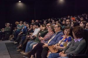 Cinema cheio com jurados, professores, alunos e familiares.