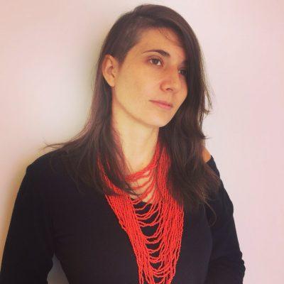 Livia Perez com Colar de contas vermelhas e Roupa preta
